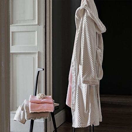 accappatoio appeso con asciugamani in diversi colori