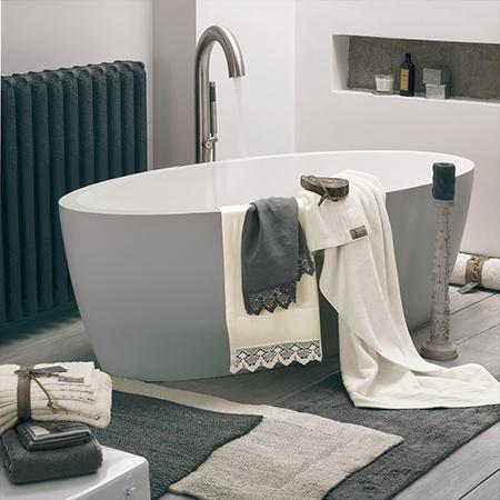 vasca da bagno con tappeti e asciugamani coordinati